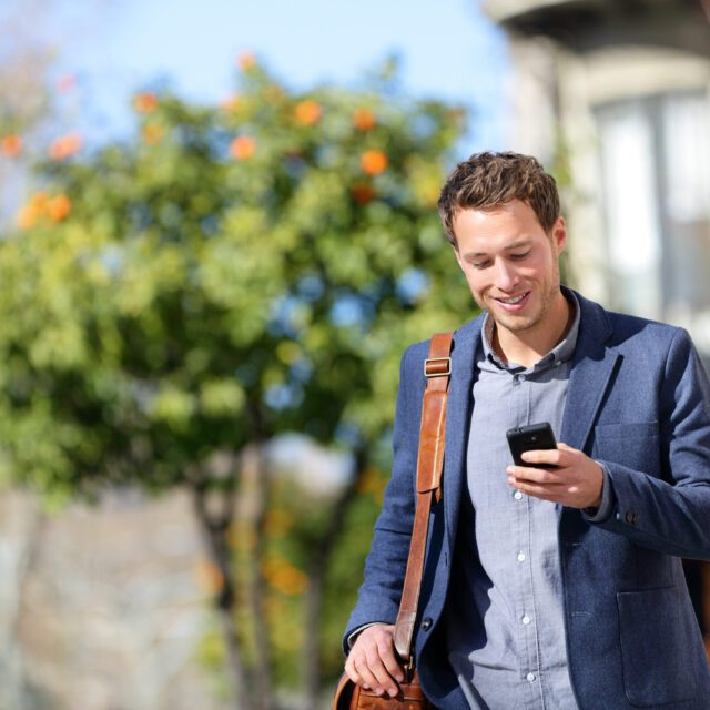 A man in a suit walking outdoors smiles as he looks at his smartphone.