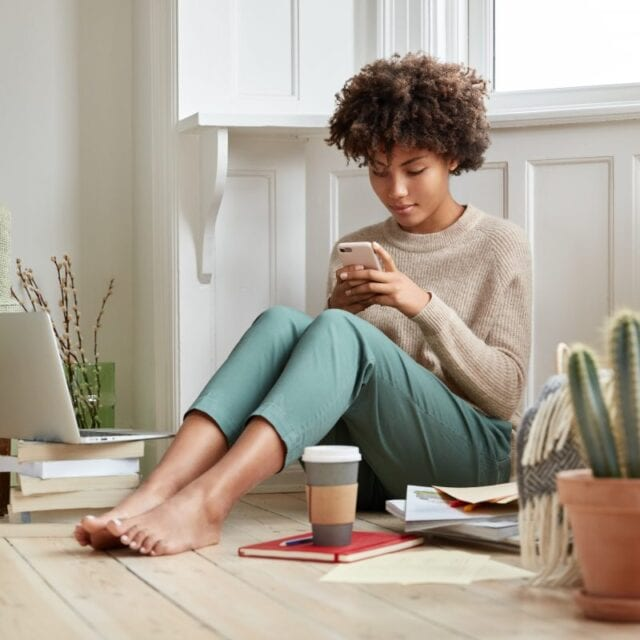 A seated young woman looks at her smartphone, updating her data security.