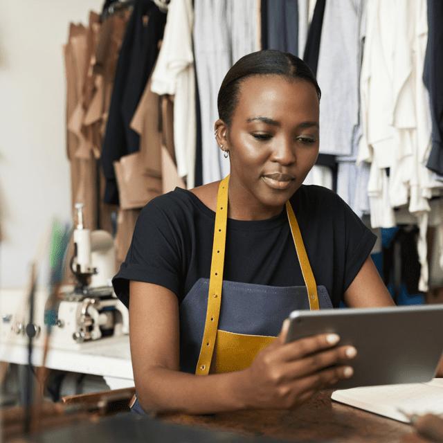 Avenir du détail Interac : Une femme vêtue d'un un tablier dans un atelier tient une tablette.